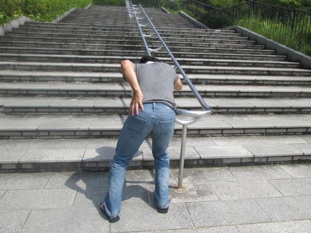 腰の痛みにうずくまる男性の写真